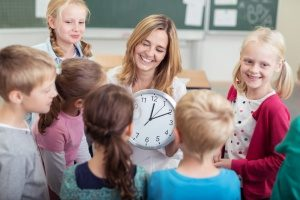 teacher holding a clock at one of the most notable preschools in northern Virginia to teach infants how time and clocks work