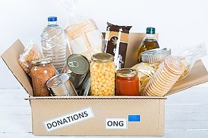 an example of spreading love through service which shows a box of food donations for local homeless shelters