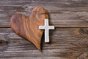 a cross that is attached to a wooden heart to symbolize how sunday worship services can increase your health