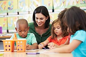 teacher assisting students with learning arts and crafts at a Christ Lutheran preschool in Fairfax, VA